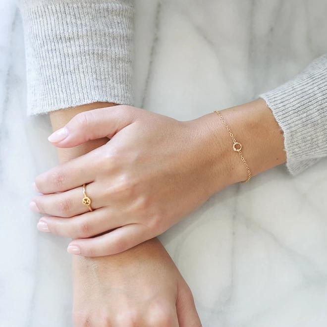 Models hands crossed while wearing the gold Circle Bracelet against a marble background.