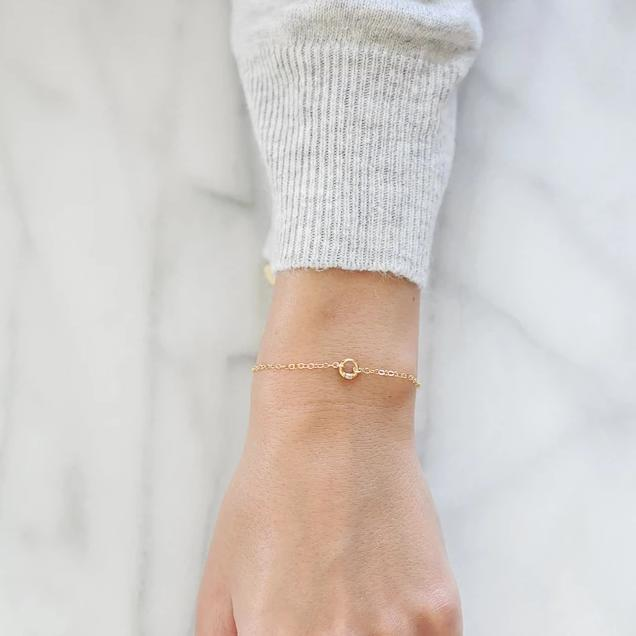 Models hand wearing the gold Circle Bracelet against a marble background.