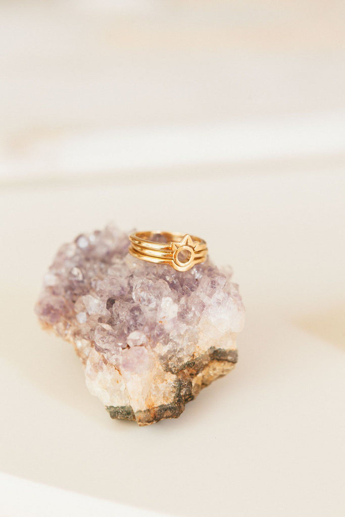 Image of the gold Sphere Ring stacked with other KDJ rings on top of a purple crystal.