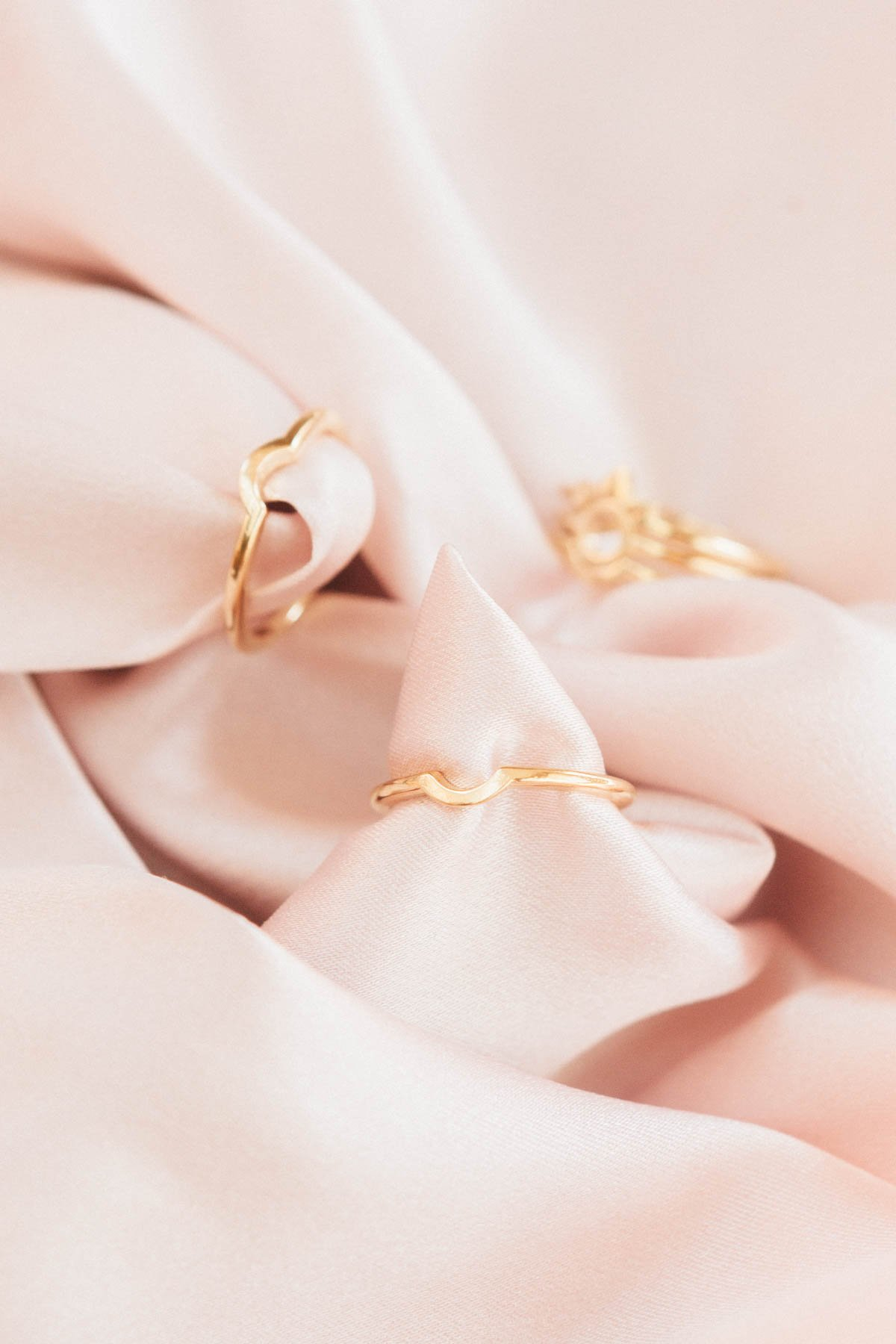Image of the gold Half Sphere Rings against blush fabric.