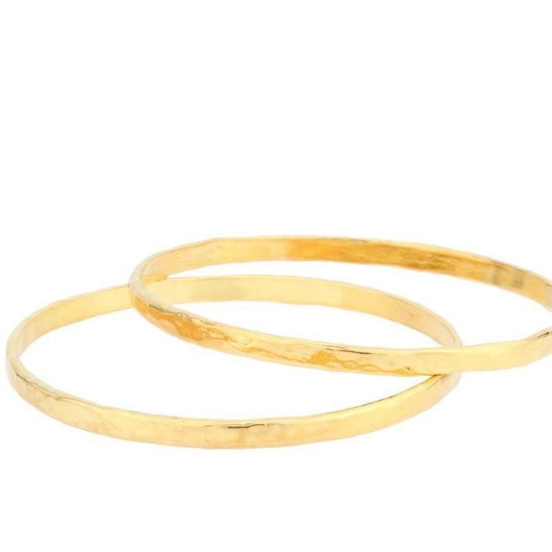 Up close image of two gold Hammered Bangles against a white background.