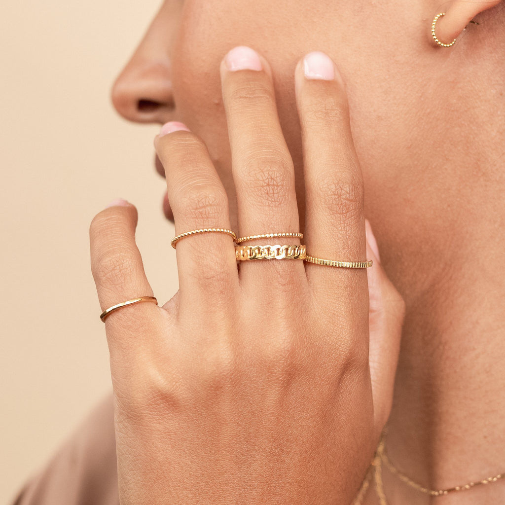 Model holding up her hand to her face, wearing dainty gold stacking rings made by Katie Dean Jewelry. Showing the Hammered Band Ring, Coin Ring, Figaro Chain ring, and Beaded Ring.