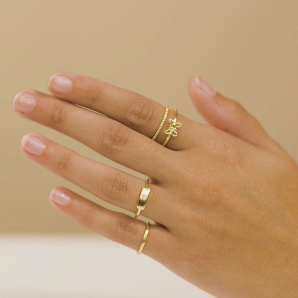 Hand model wearing dainty golden rings, hammered Band ring, Rectangle Ring, Beaded Ring and Butterfly ring, Katie Dean Jewelry