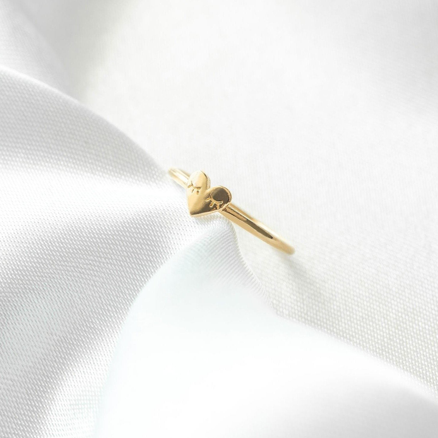 Dainty gold heart ring with eyelashes on the heart, sitting on a white piece of satin.