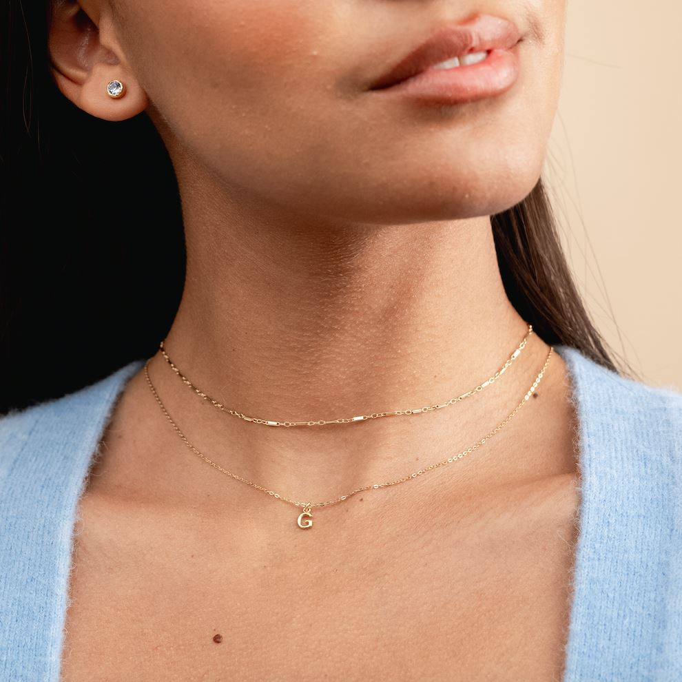 Model wearing the dainty gold linked choker and initial necklace, handmade by Katie Dean Jewelry