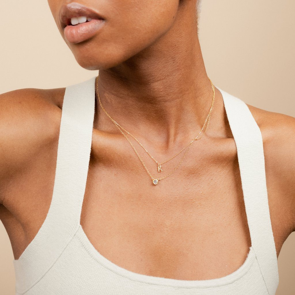 Model wearing the dainty gold Initial Necklace and Birthstone Necklace, handmade in America by Katie Dean Jewelry