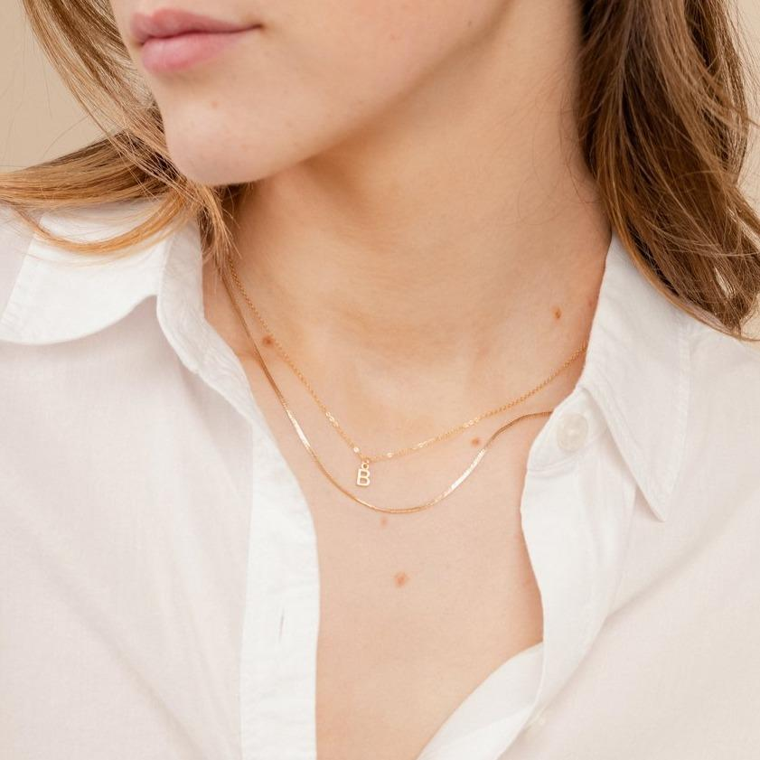 Model wearing the dainty gold Initial Necklace and Herringbone Chain Necklace, handmade in America by Katie Dean Jewelry