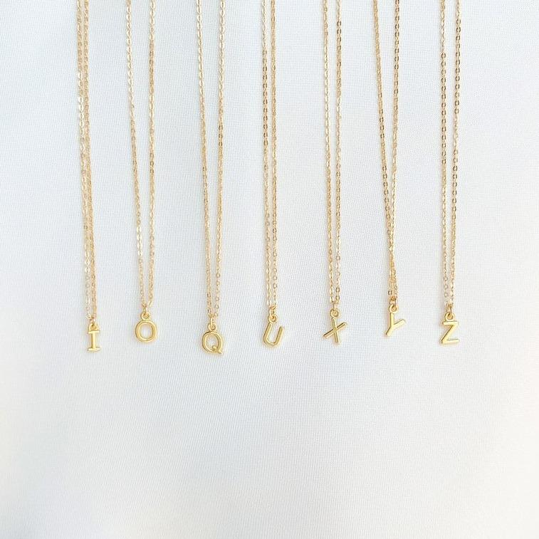 Initial Necklaces on white satin, Initials I O Q U X Y Z, made by Katie Dean Jewelry