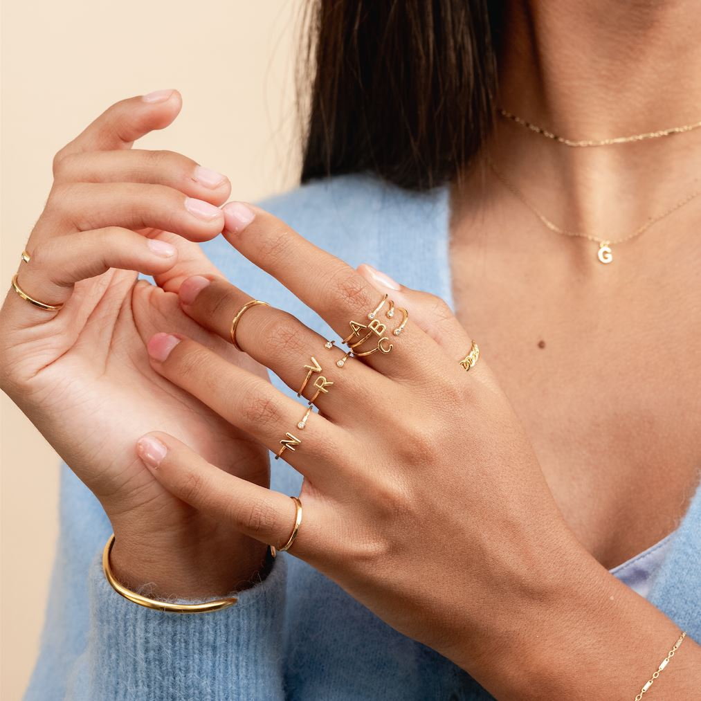 Two hands showing in the center of the image wearing the Initial Rings and Hammered Band Rings made by Katie Dean Jewelry.