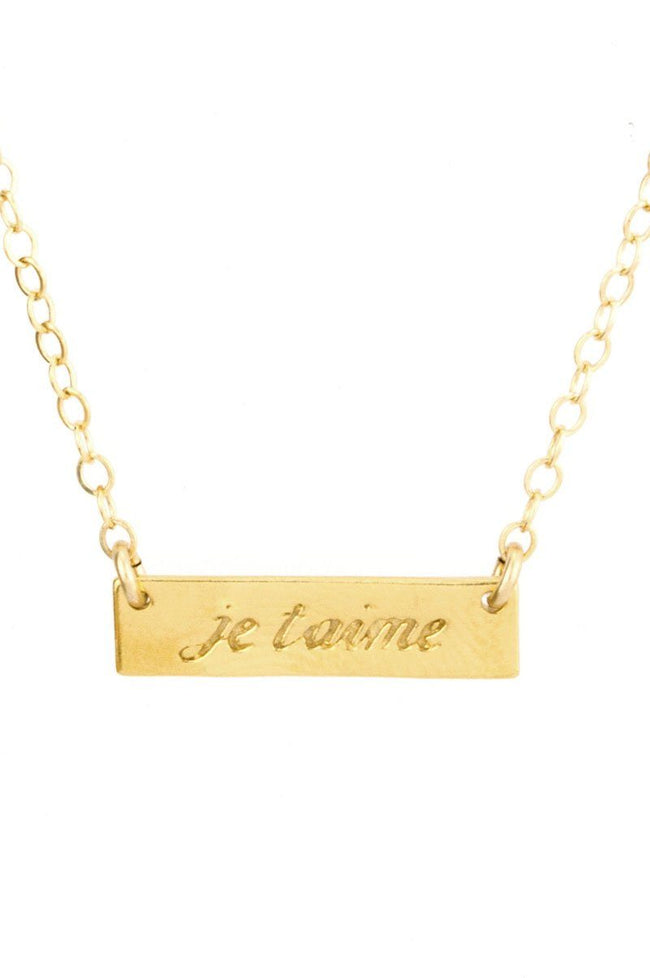 Up close image of the gold Je Taime Necklace pendant.