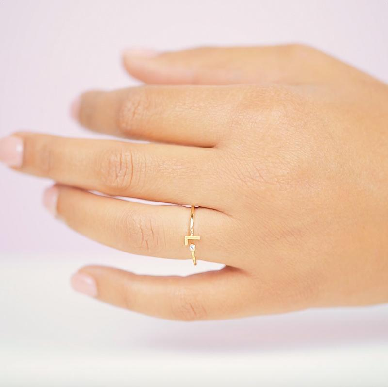 Dainty gold L Initial Ring shown on a hand against a pink background