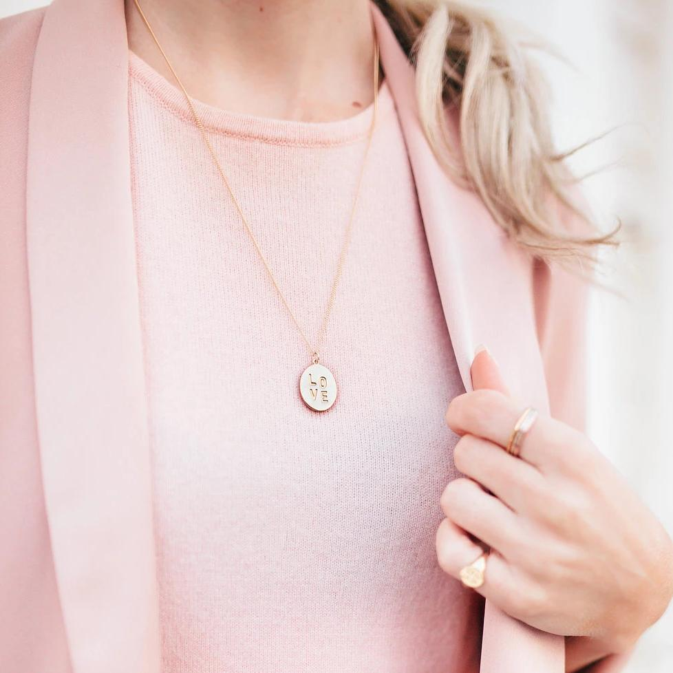 Katie Dean model wearing the gold Love Charm Necklace with a blush top.