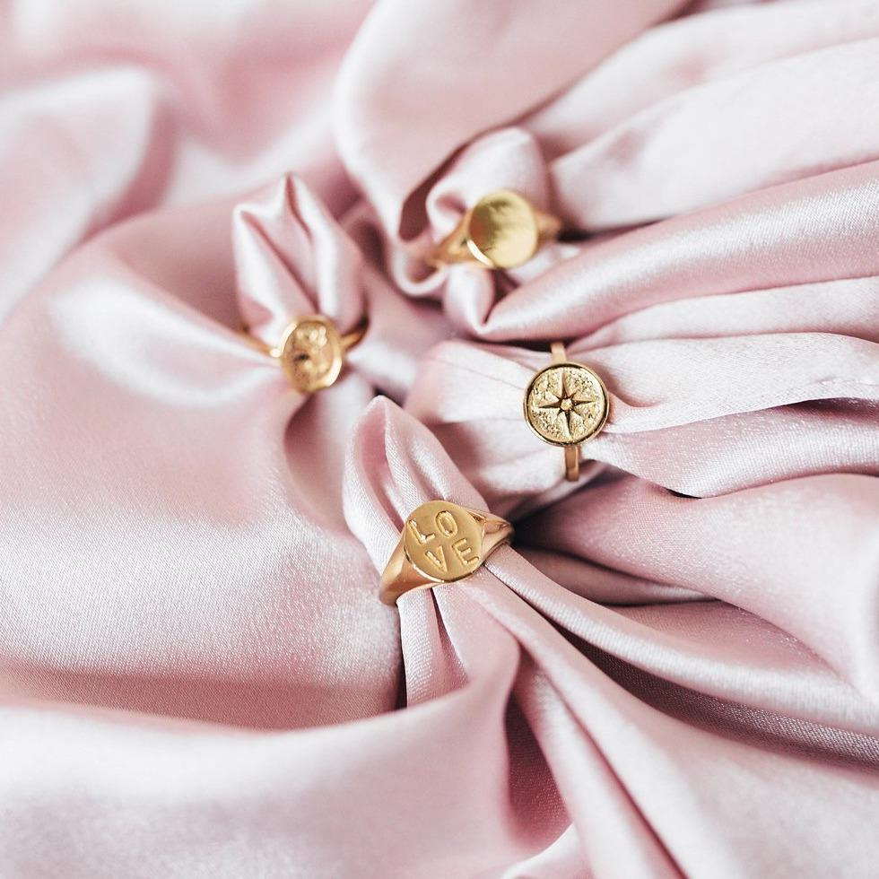 Gold Love Signet Ring artfully placed on pink satin.