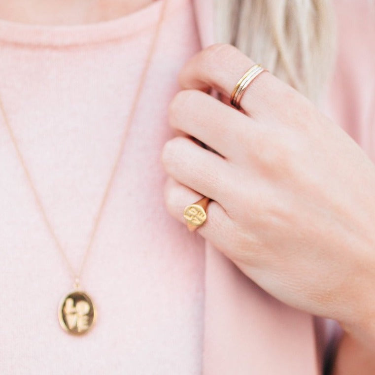 Love Signet Ring worn as a pinky ring, with 18k yellow gold plating.