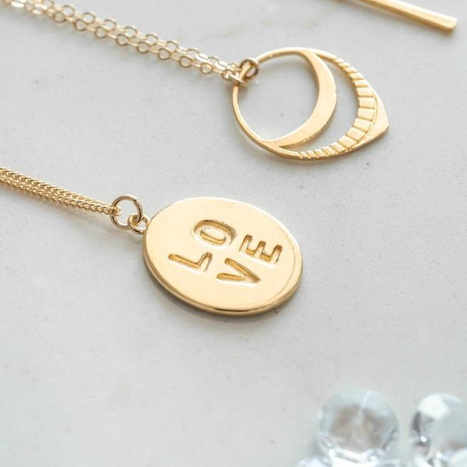 Flat oval charm with the letters LOVE imprinted on top of the gold charm.