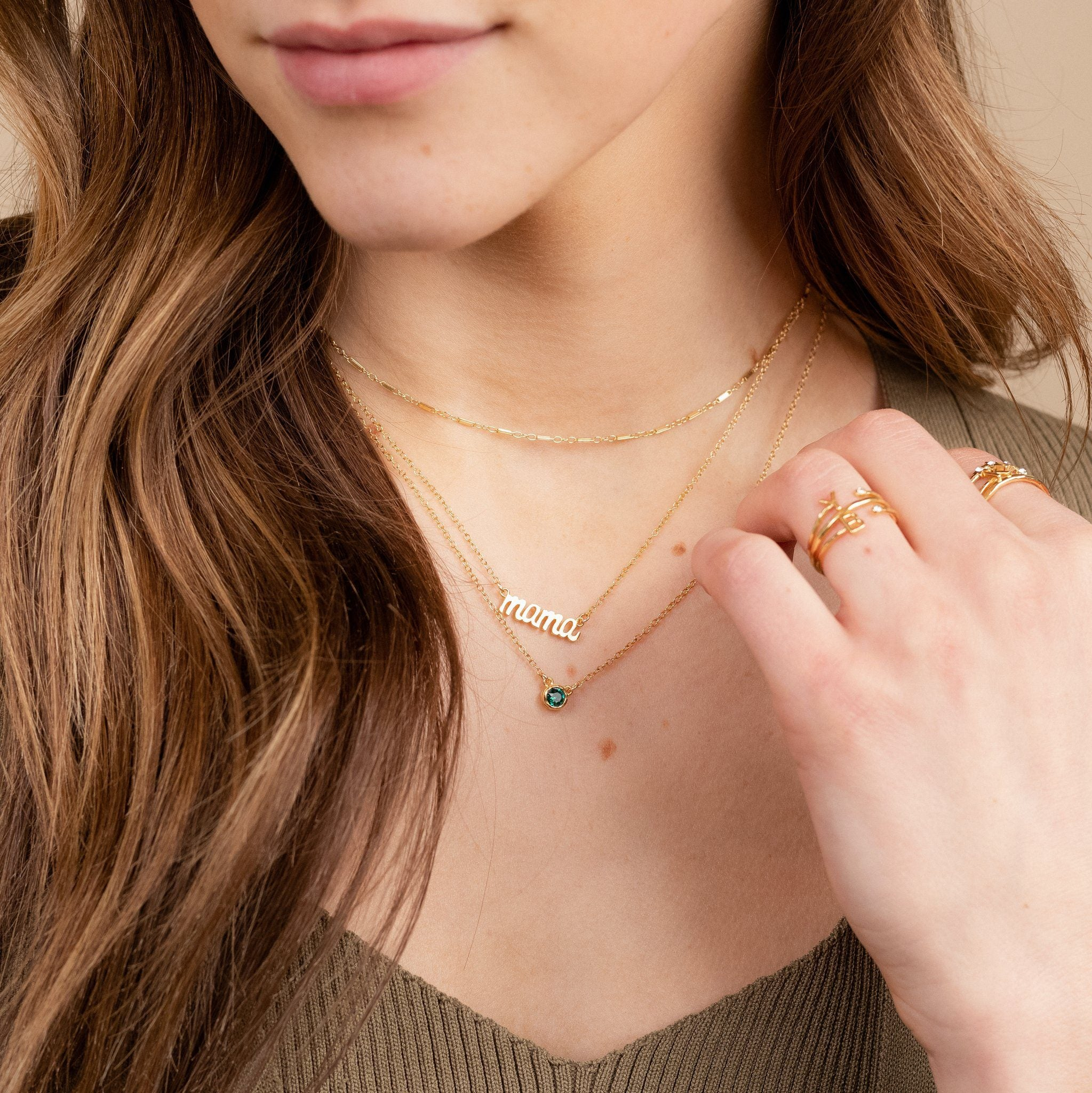 Dainty gold Mama Necklace layered with the Link Choker, and May Birthstone Necklace by Katie Dean Jewelry