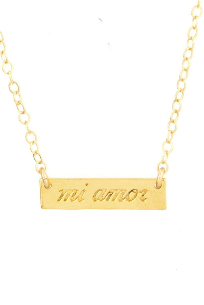 Up close image of the gold Mi Amor Necklace pendant with writing.