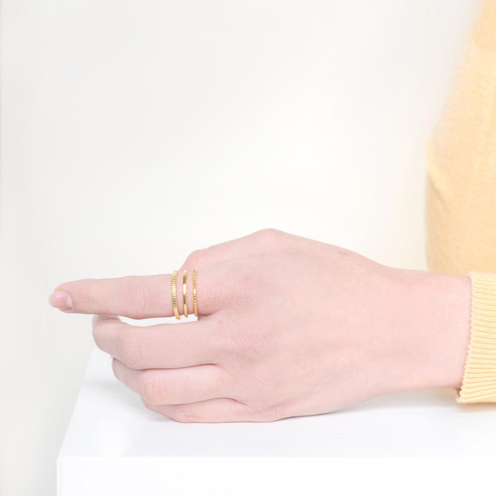 Image of models hand wearing the gold Minimal Stack against a white background.