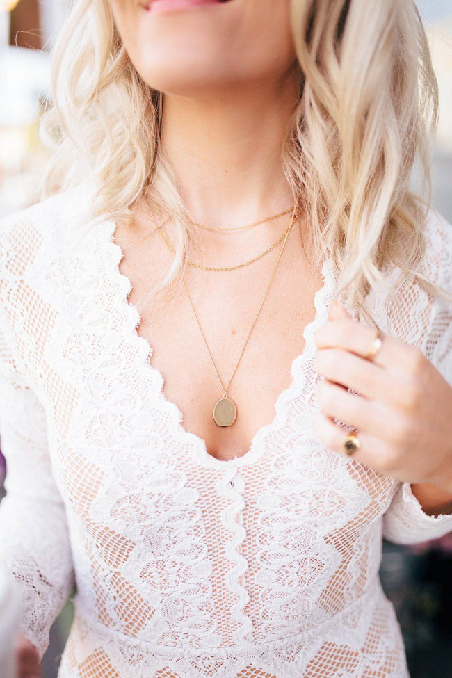 Image of model wearing the gold Duo Layer Necklace in a white top.