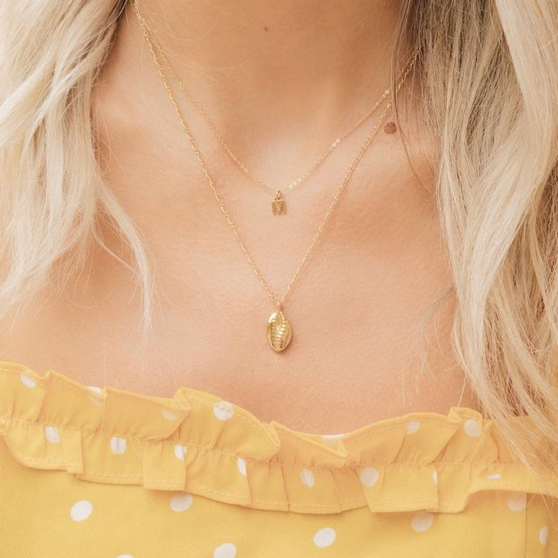 "Puka Shell Necklace, gold and dainty layered with an Initial ""M"" Necklace also gold. Model has blonde hair and is wearing a yellow dress with white polka dots."