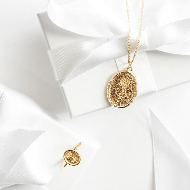 Rose Charm Necklace in gold on top of a white gift box as well as a dainty Rose Ring next to it.
