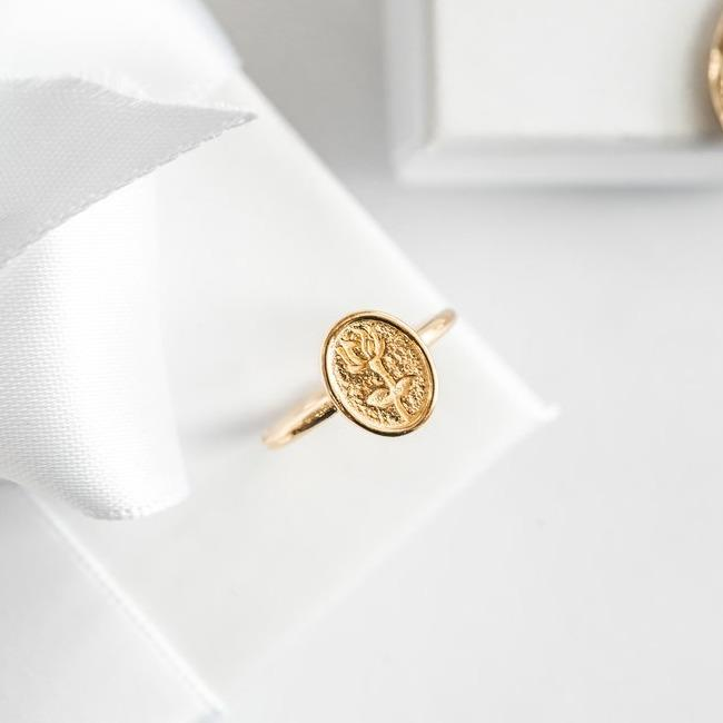 Gold Rose Ring sitting on a white gift box.