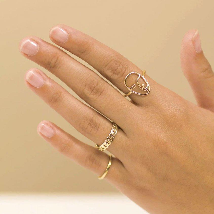 Dainty gold rings handmade by Katie Dean Jewelry, featuring the Artist Face Ring, Figaro Chain Ring and Hammered Band Stacking Ring.