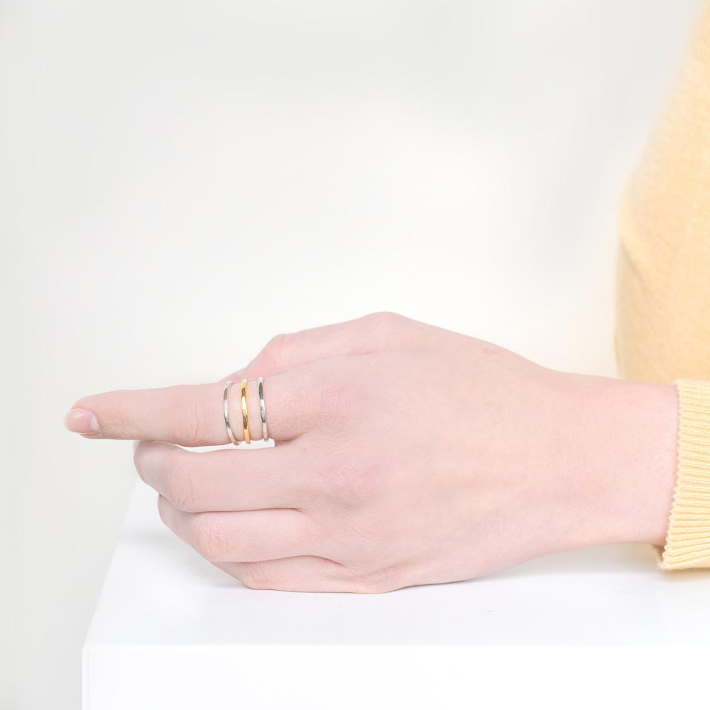 Image of models hand wearing the Silver & Gold Stack.