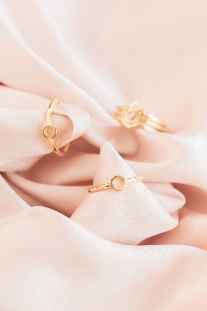 Image of the gold Sphere Ring beside other gold KDJ rings against blush fabric.