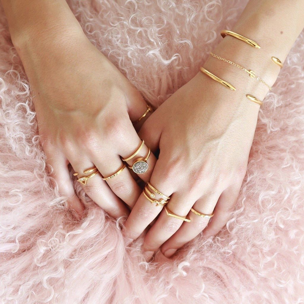 Gold rings layering on the hands of a model on a pink pillow, made by Katie Dean Jewelry
