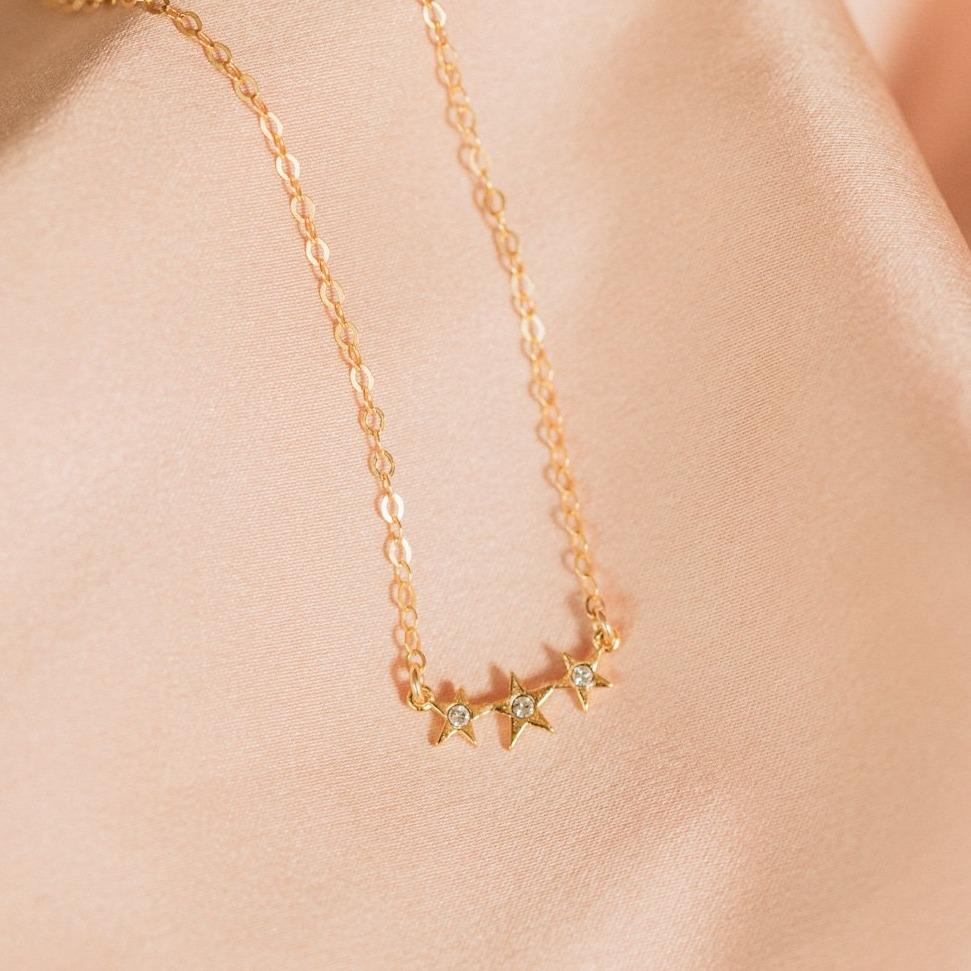 Three charm with a small Swarovski Crystal in the middle of each star, laying on a pink piece of satin.