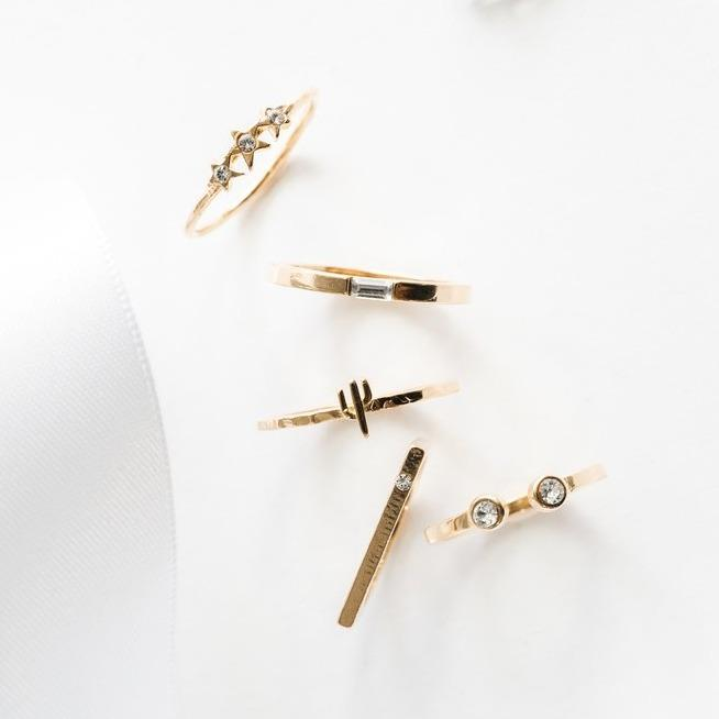 Dainty gold Starburst Ring alongside a Cactus Ring, Baguette Ring, Bar with Gem Ring and Two Gem Ring
