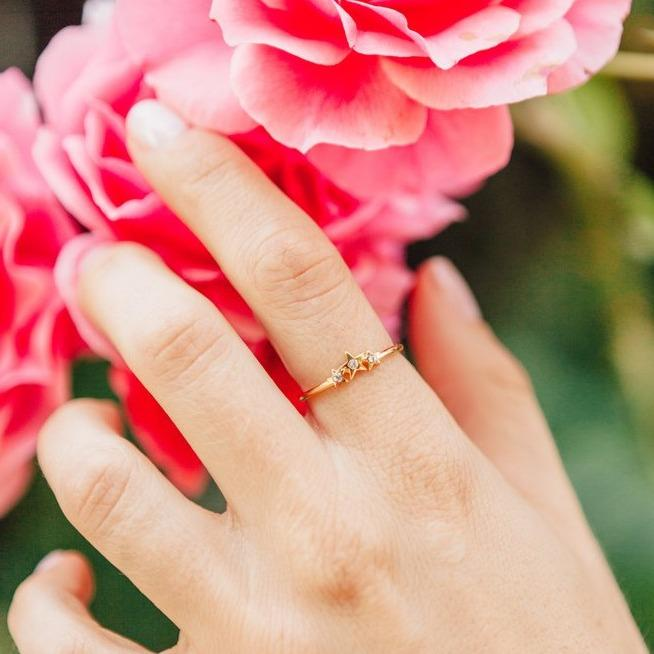 Starburst Ring, dainty and gold, as seen on the index finger while model's hand reached for pink roses.