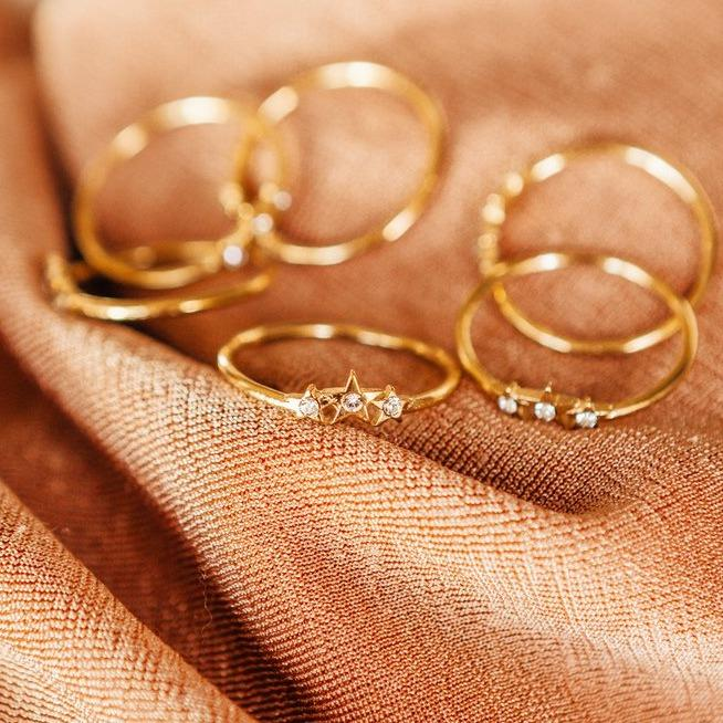 Dainty gold Starburst Rings on a salmon cloth.