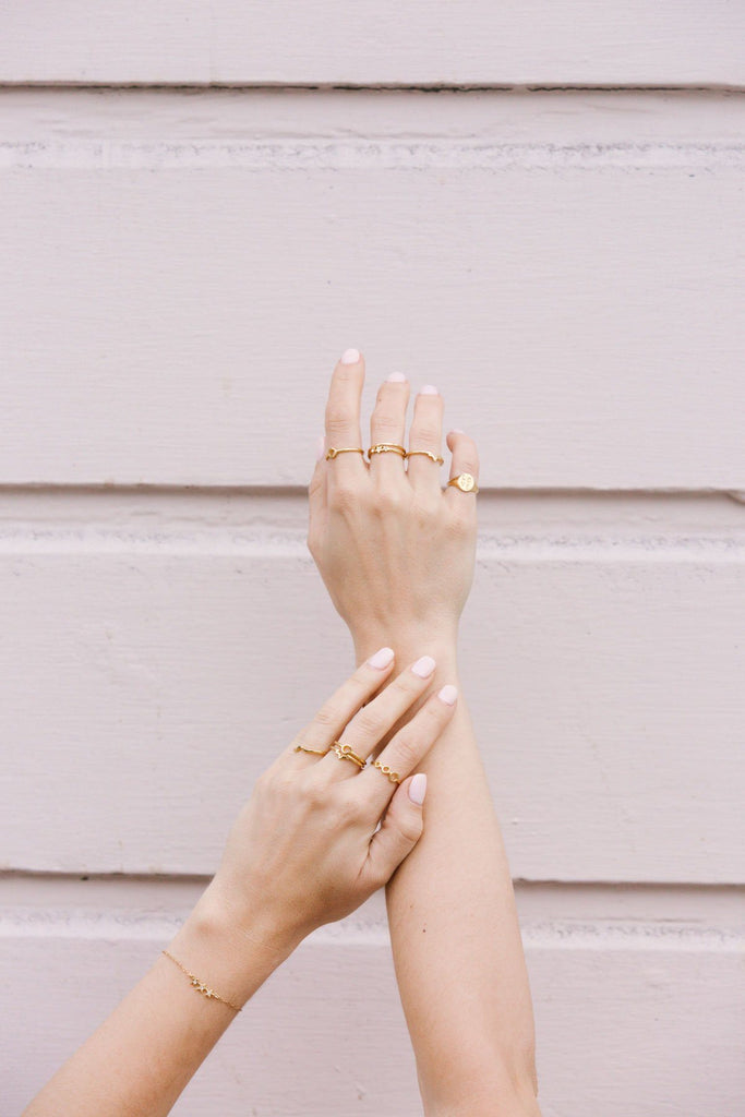 Image of models hands wearing the gold Sphere Ring with other gold KDJ rings.