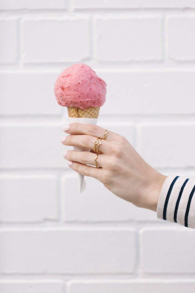 Image of models hand holding an ice cream cone while wearing the gold Half Sphere Ring.