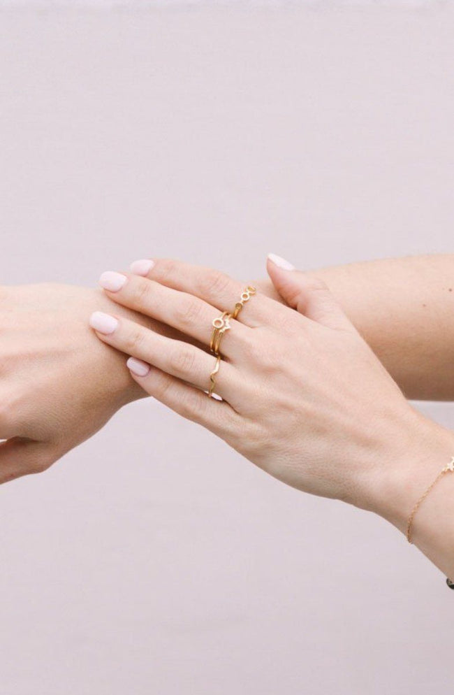 Image of models hands while wearing the gold Trio Ring.