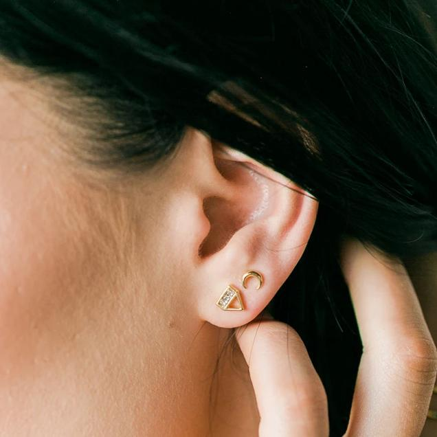 Image of models ear wearing a gold Love Triangle Stud.