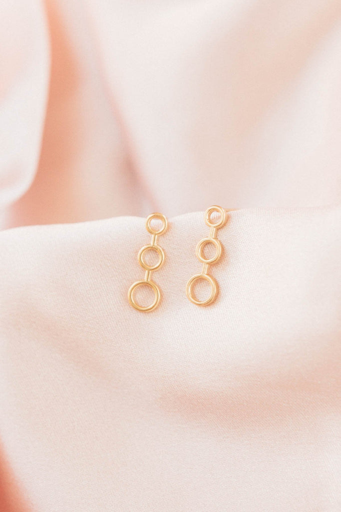 Image of the gold Trio Studs against a blush background.