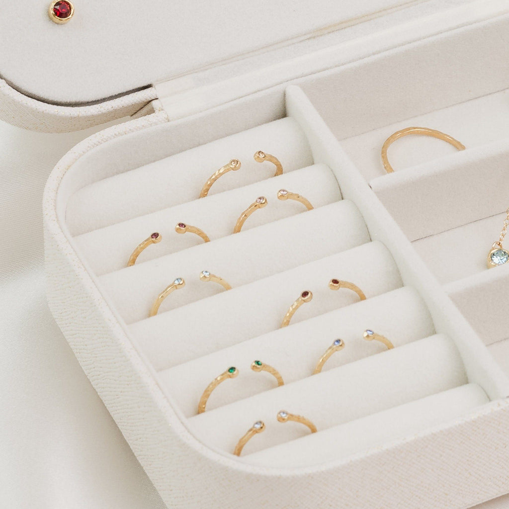 White jewelry case with birthstone collection with a close up of the Birthstone Rings, shown on satin katie dean jewelry