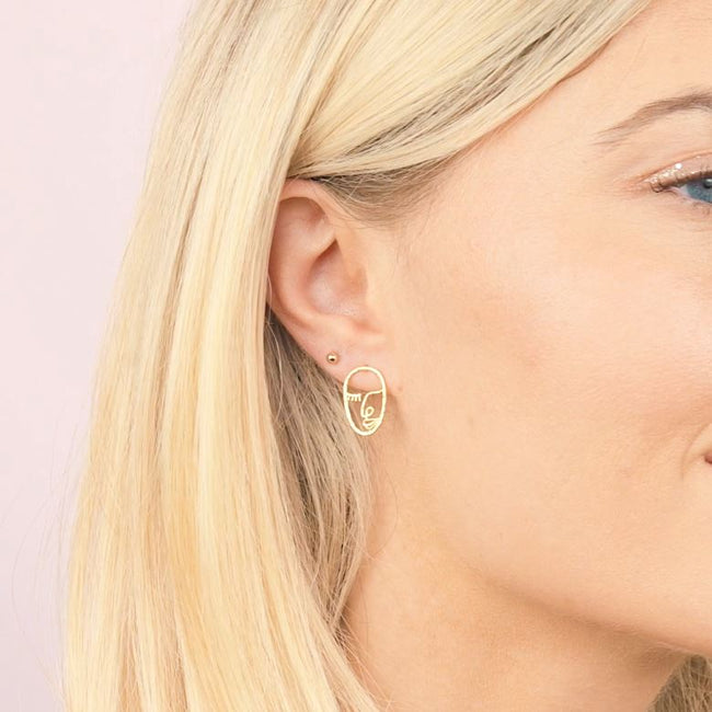 Model wearing the Beaded gold stud earring and the Artist Face Earring inspired by Matisse and Picasso. Handmade in California by Katie Dean Jewelry. Nickel free and hypoallergenic.