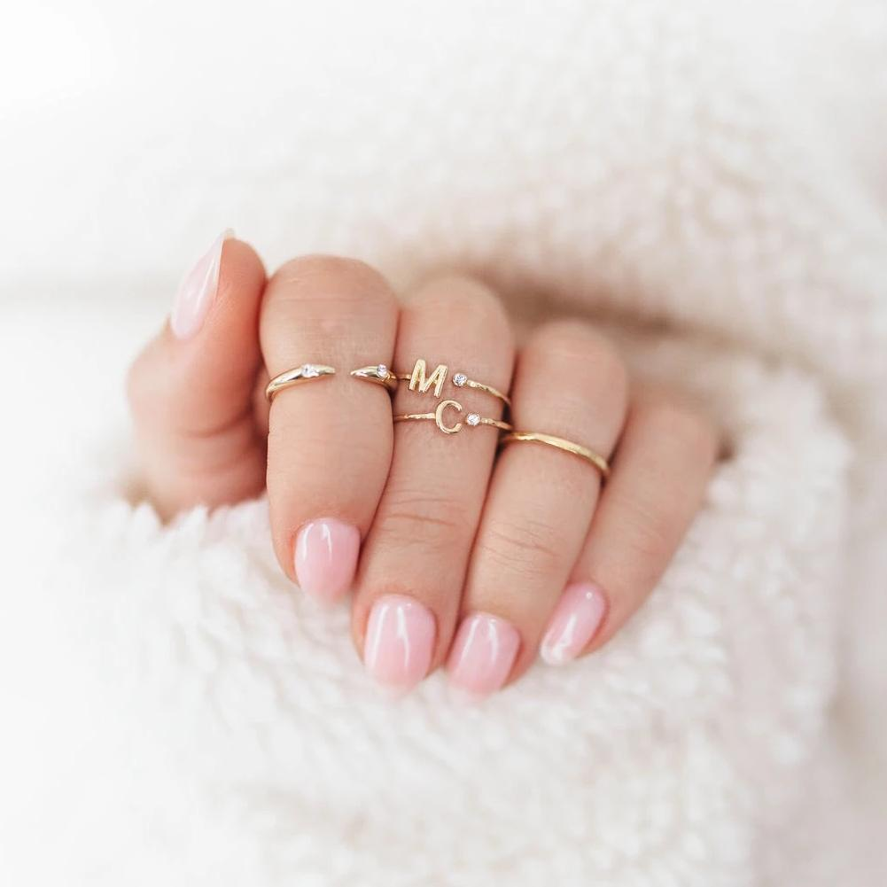 Dainty gold Initial M and C Rings shown on a hand wearing a white sweater