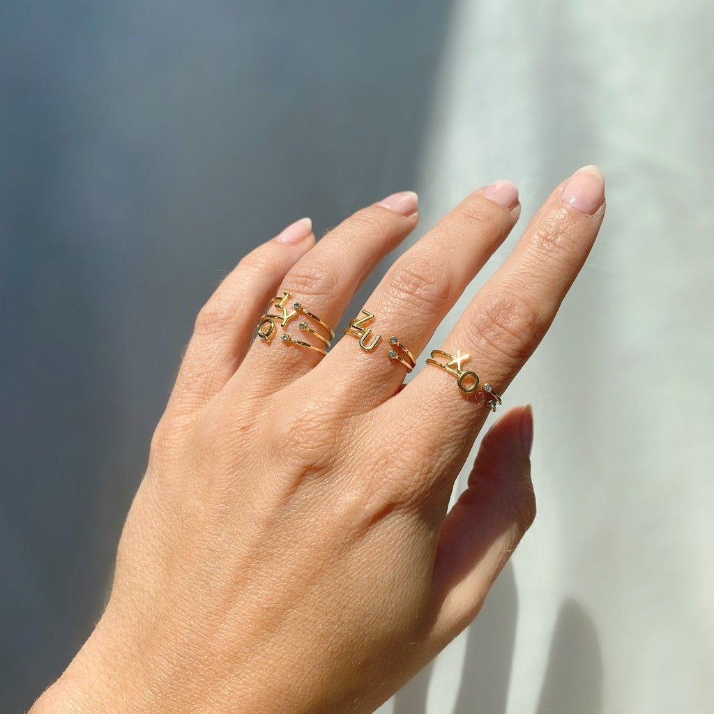 Dainty gold Initial Rings i, o, q, u, x, y, z sparkling in the sunlight as shown on a hand with a piece of white satin behind.