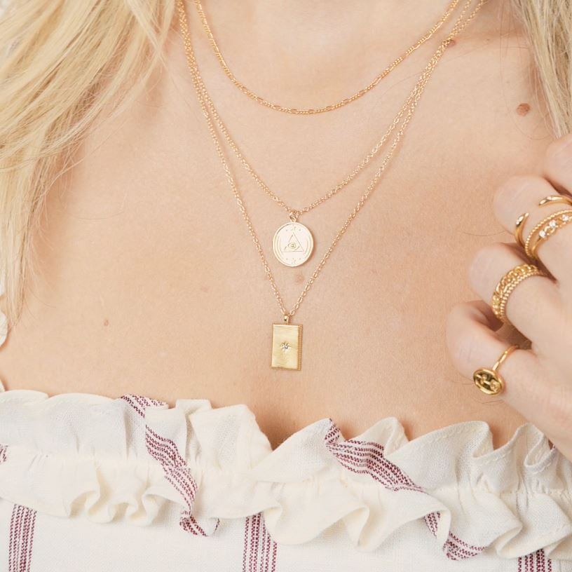 Model wearing three layered gold dainty necklaces. Top is a plain chain, middle is a circular charm necklace, bottom is a rectangle charm necklace. All gold in color.