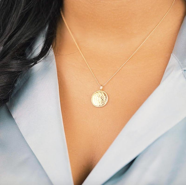The Beaded Coin Necklace. The beaded edging and hammered finish on this coin charm makes it glisten beautifully in the light. It also layers perfectly with the Beaded Arch Necklace. Handmade in California by Katie Dean Jewelry.