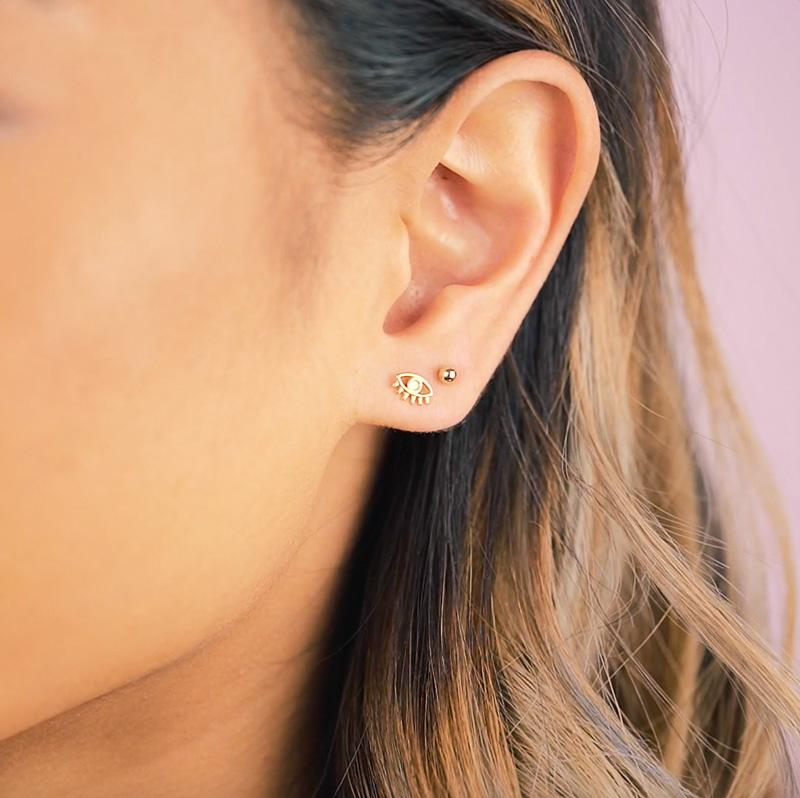 Image of the left side of the face showing an ear with two piercings, one with a gold eye earring and another with a small ball bead earring.