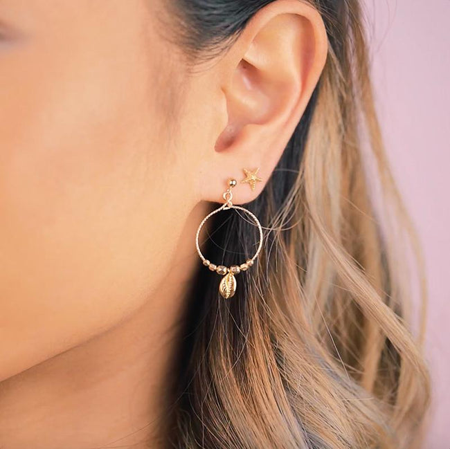 Whimsical, tropical and perfectly beachy. These Puka Shell Hoop Earrings will take you on a summer getaway even if you're heading into the office for a full day of work. Handmade in California by Katie Dean Jewelry.