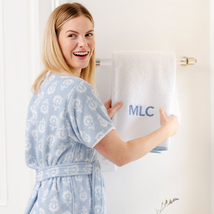 Model is wearing the womens short patterned robe in a Tullie pattern. Model is holding a piped edge bath towel with light blue piping, and MLC embroidered in French Blue thread and Tybee font.