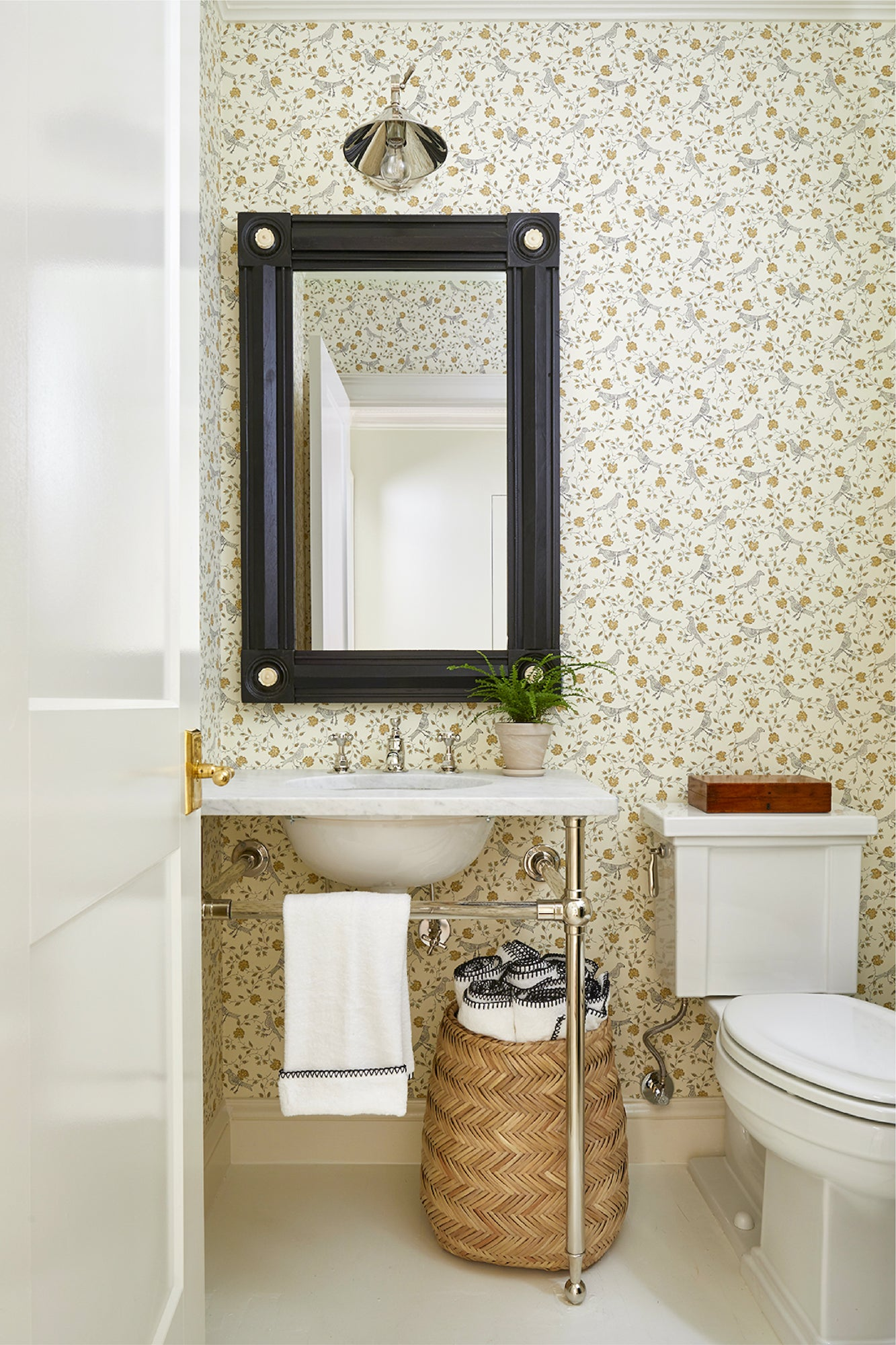 A bathroom Jeremy designed with floral wallpaper and black edged Weezie towels.