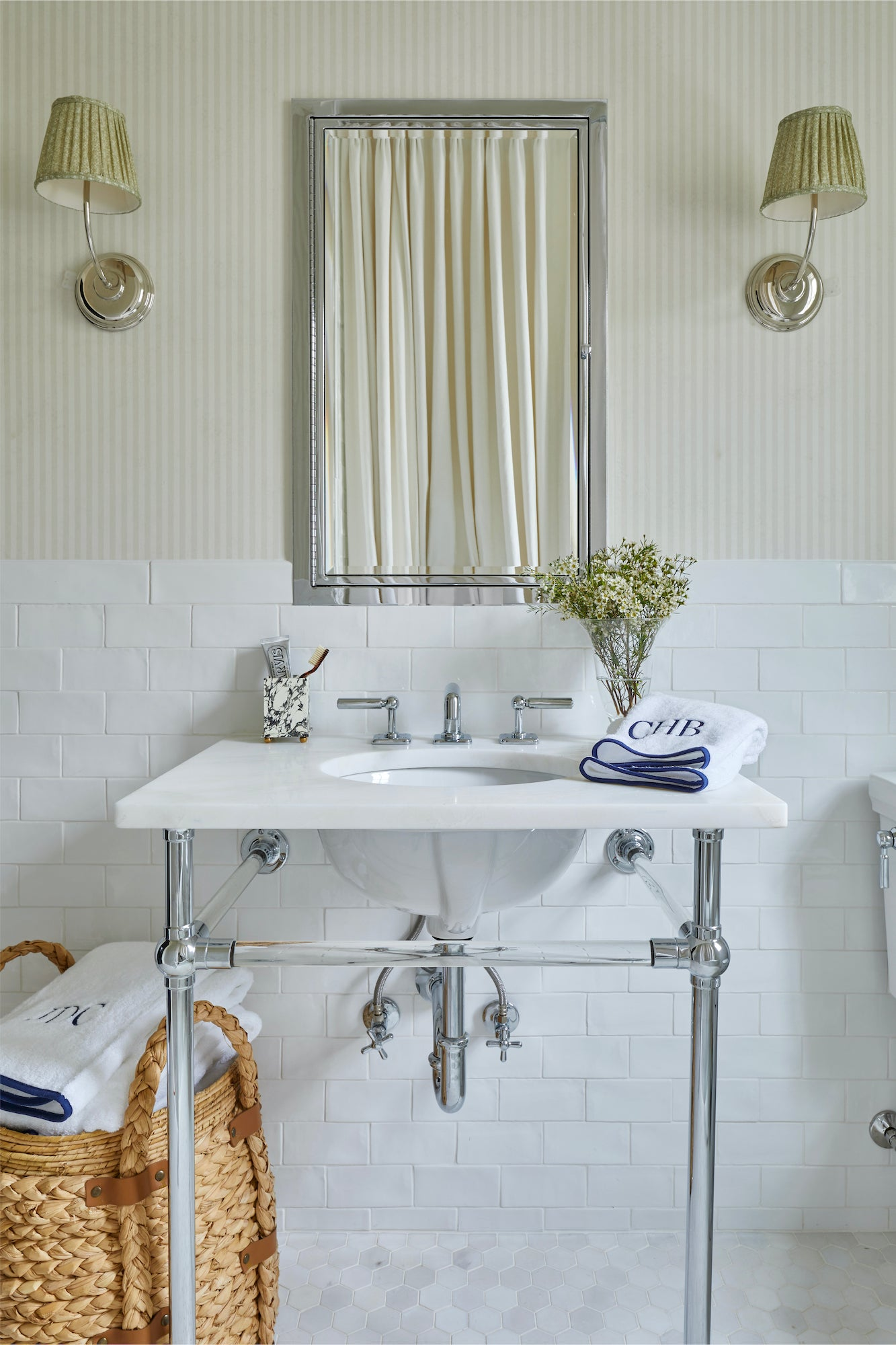 A bathroom Jeremy designed with cream striped wallpaper and navy piped towels.